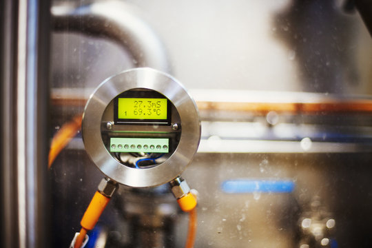 Close up of a gauge with a digital print out in a brewery.