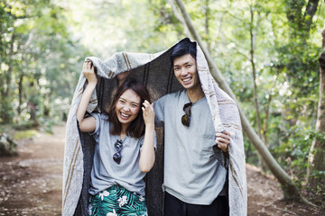 Young woman and man standing in a forest, holding a blanket over their heads.