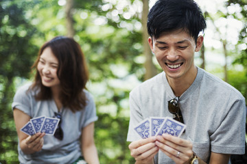 Young woman and man sitting in a forest, playing cards.