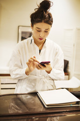 Woman working in fashion boutique, using mobile phone