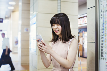 Smiling young woman with long brown hair, holding a mobile phone.