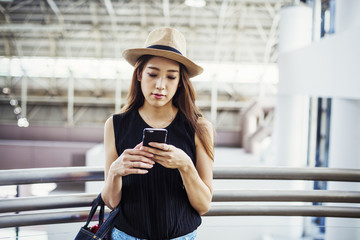 Young woman with long brown hair, wearing a Panama hat, in a shopping centre, using a mobile phone.
