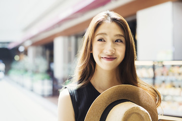 Smiling young woman with long brown hair, holding Panama hat.