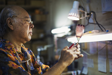 A senior craftsman at work in a glass maker's studio workshop, in inspecting red wine glass with cut glass decoration against the light.