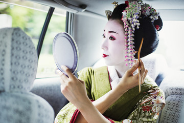 A woman dressed in the traditional geisha style, wearing a kimono and obi, with an elaborate hairstyle and floral hair clips, with white face makeup with bright red lips and dark eyes in a car using a hand mirror.