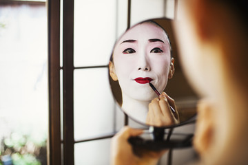 Geisha woman with traditional white face makeup applying bright red lipstick with a brush, using a mirror.
