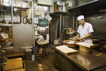 A small artisan producer of wagashi. A man mixing a large bowl of ingredients and pressing the mixed dough into moulds in a commercial kitchen.