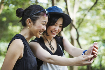 Two young women standing in a forest, taking a selfie.