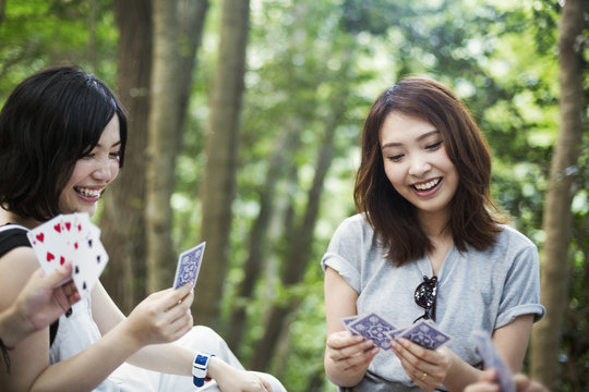 Two young women sitting in a forest, playing cards.