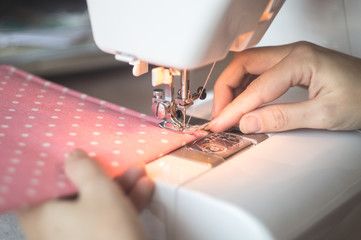 Female hands working on a white sewing machine with pink cloth