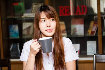 Portrait of thai adult student university uniform beautiful drinking coffee