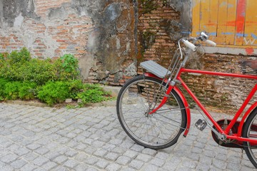 Vintage Red bicycle near the window of old brick wall