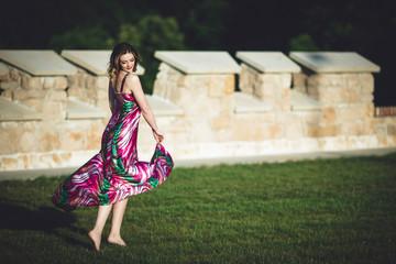 joyful girl dancing on a green meadow
