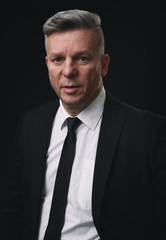 Serious senior businessman in black suit