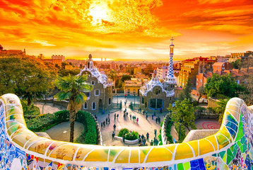 View of the city from Park Guell in Barcelona, Spain, at sunrise with golden sky.