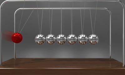 Balancing ball Newton's cradle pendulum with motion blur over dark background
