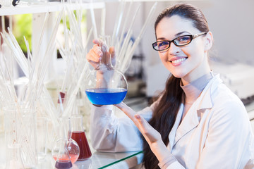 Female scientist in a laboratory holding a jar with liquid