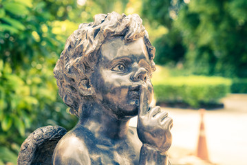 Cupid statue in green garden. Vintage filter style