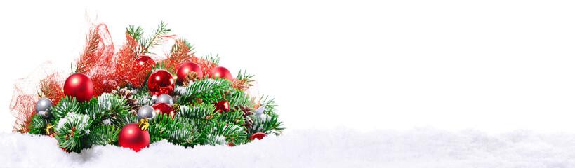 Tannenzweige mit Weihnachtsdekoration auf Schnee