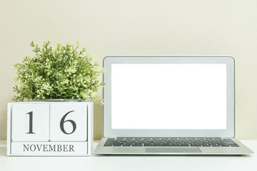 White wooden calendar with black 16 november word with white blank space at center of computer notebook on white wood desk and cream wallpaper textured background , selective focus at the calendar