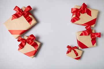 Christmas presents wrapped in brown paper with red silk bows on a soft grey background with blank space in middle