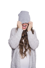 Modern teenage girl in  beanie hat and gray sweater. Fashionable young woman posing. Studio portrait isolated white background. Screaming model.