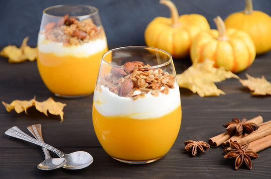 Pumpkin dessert with yogurt and homemade granola on dark wooden table, selective focus