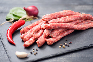 Raw beef sausages, chilly and spinach on the black desk.