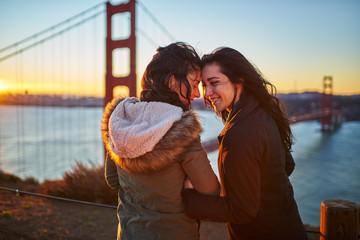 happy romantic female couple at golden gate bridge