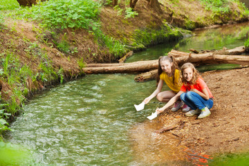 Two girls launching paper boats from riverside