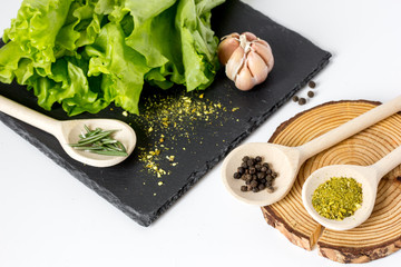 various spices in spoon with wooden stand on white background