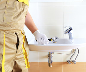 Plumber in uniform in bathroom