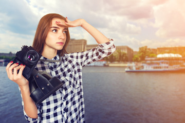 Portrait of a pretty woman  traveler in plaid shirt holding an old camera in hands standing over .and looks into the distance background of   river and boat floats Moscow, Russia