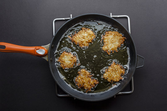Frying latkes with ready side up in deep oil on the pan from above