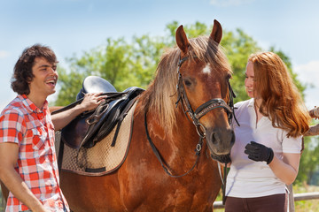 Young couple spending time together with horse