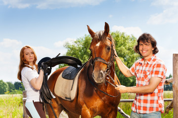 Young man and woman saddling their bay horse