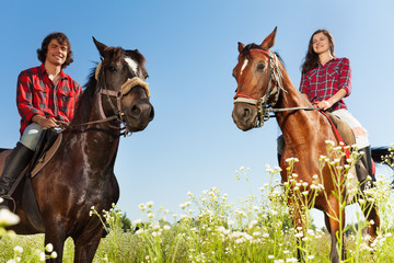Young people horseback riding in flowery meadows