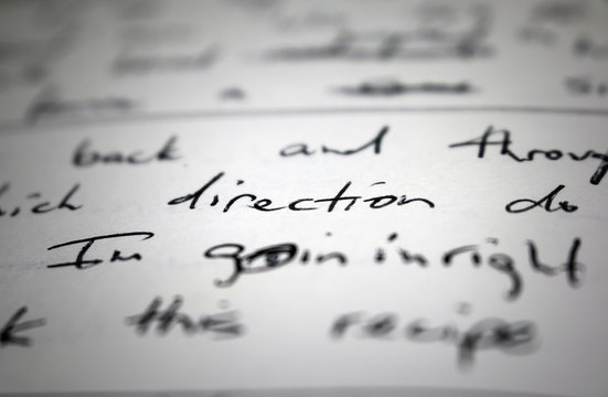 "Lyrics written on paper in black ink close up. Focus on the word ""direction"" and ""I'm goin in"""