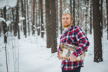 the man in the plaid shirt carries firewood