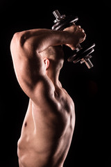 muscular man bodybuilder lifting weight, training triceps, isolated on black background