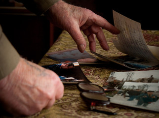 Elderly man Hands sift through old photographs on the table