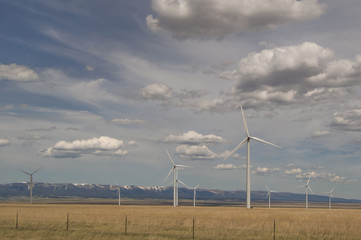Judith Gap windmills that are part of a large renewable energy wind farm with mountains in the background, prairie in the foreground and cloudy skies above.