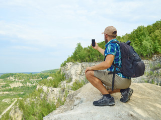 Man tourist is using a smartphone while sitting on the edge of a
