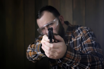 man with put on protective goggles and ear training in pistol sh