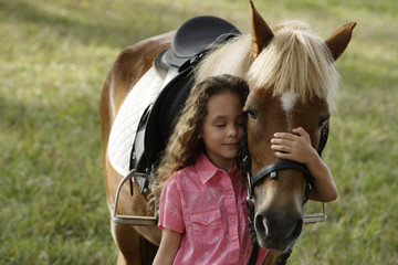 Young girl hugging nose of pony