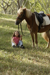 Young girl sitting under pony, holding reigns