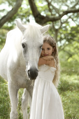 Young girl hugging white horse