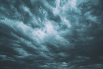 Dark turquoise blue dangerous stormy cloudy sky background.