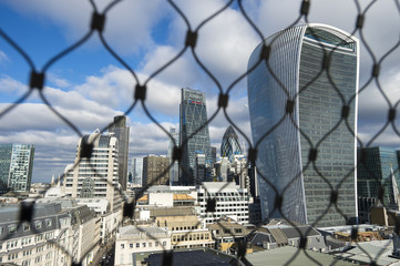 Scenic view of the City of London financial center skyline as viewed through a wire enclosure