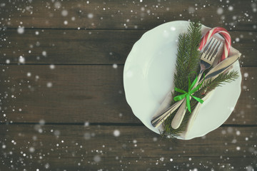 Country style christmas decoration. White empty plate with fir tree, candy, fork and knife tied with a green ribbon on old wooden brown background.